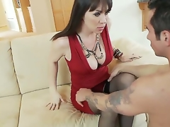 Hawt and breasty black haired milf in sexy red dress RayVeness gets her hairless taco licked on the couch in her living room by a horny young black haired fellow Joey Brass and enjoys