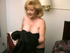 Lustful blonde grandma Kitty Fox stripping and showing her sexy decolletage